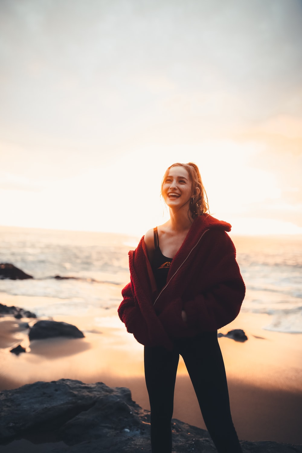 smiling woman standing beside sea