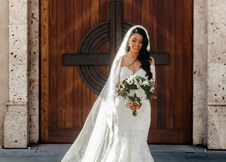 woman wearing wedding dress holding bouquet of flowers