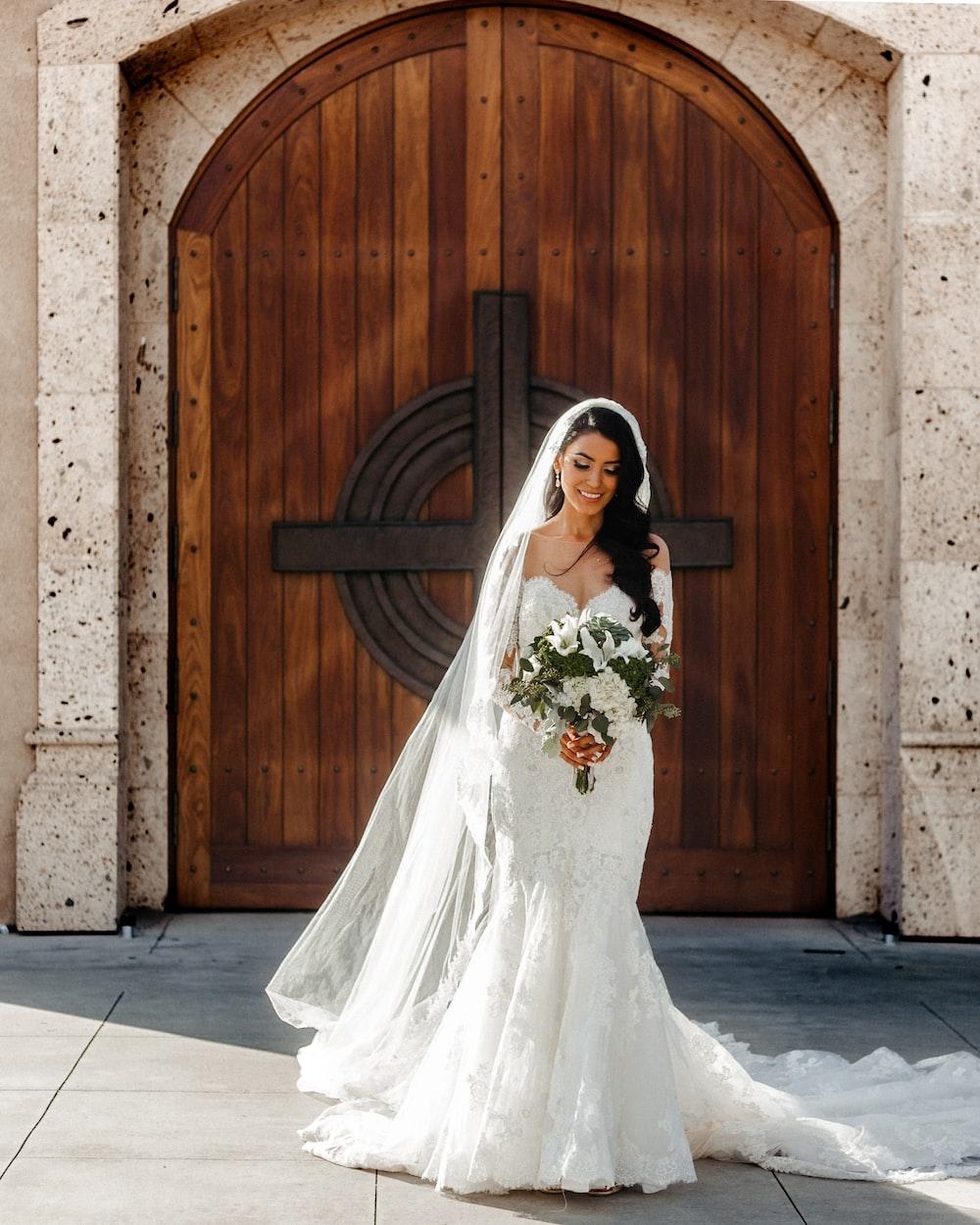 woman wearing wedding dress holding bouquet of flowers