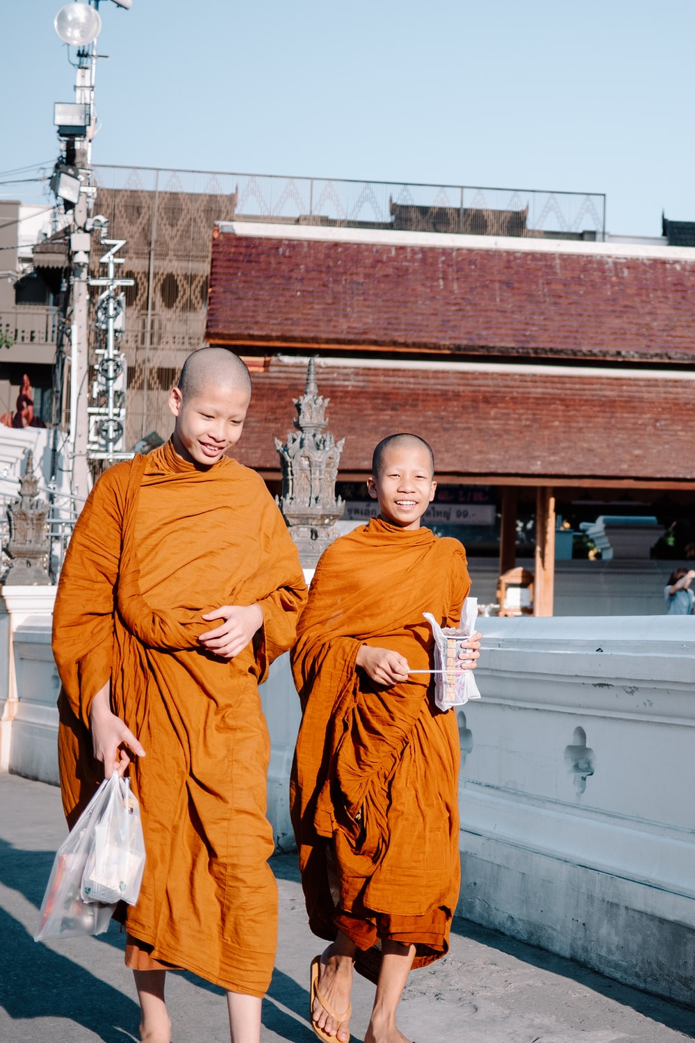 two boys monk carrying white plastic bags