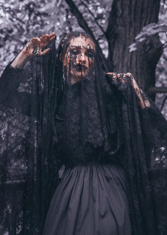 woman wearing lace veil under tree