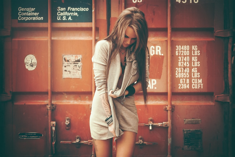 woman standing in front of red shipping container while looking down