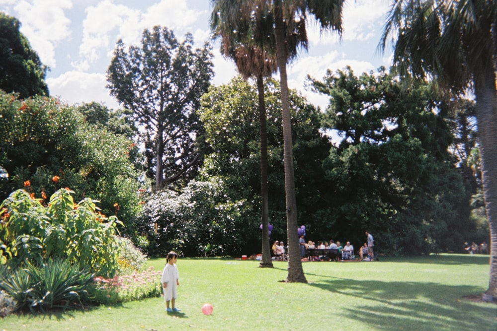 girl standing near palm trees