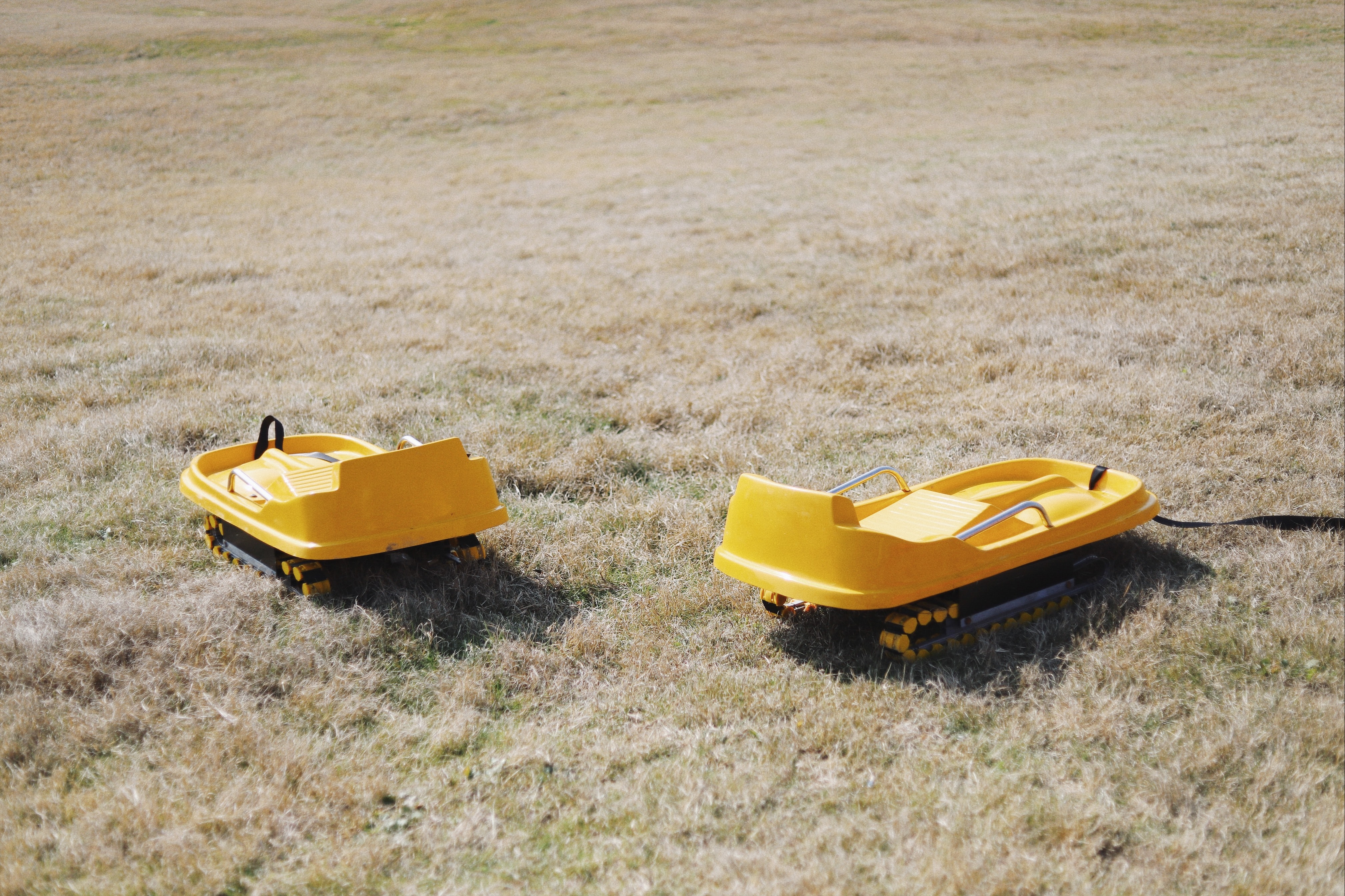 two yellow vehicle toys on green grass field