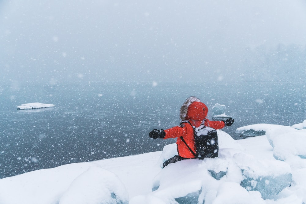 person in red hoodie sitting on snowfield
