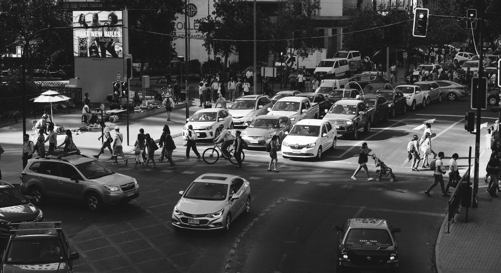 grayscale photography of people crossing on street