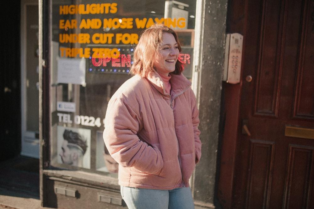 smiling woman wearing pink zip-up jacket standing near brown wooden door