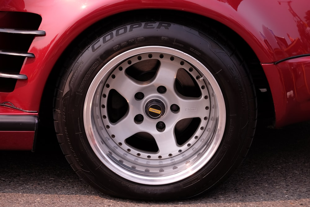 close-up photography of gray multi-spoke wheel and Cooper tire