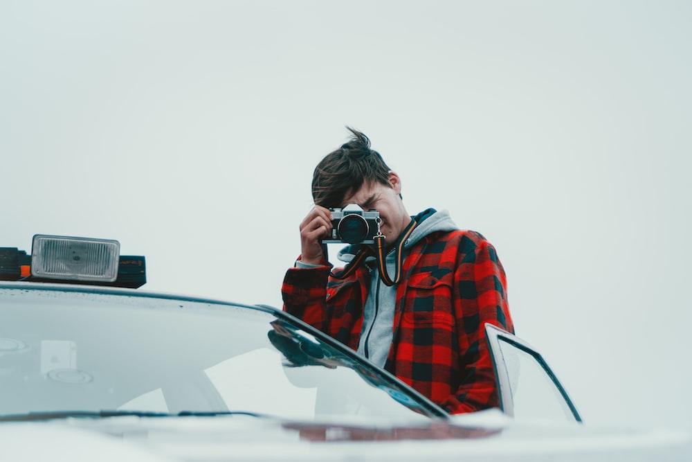 man standing near open door of car using camera