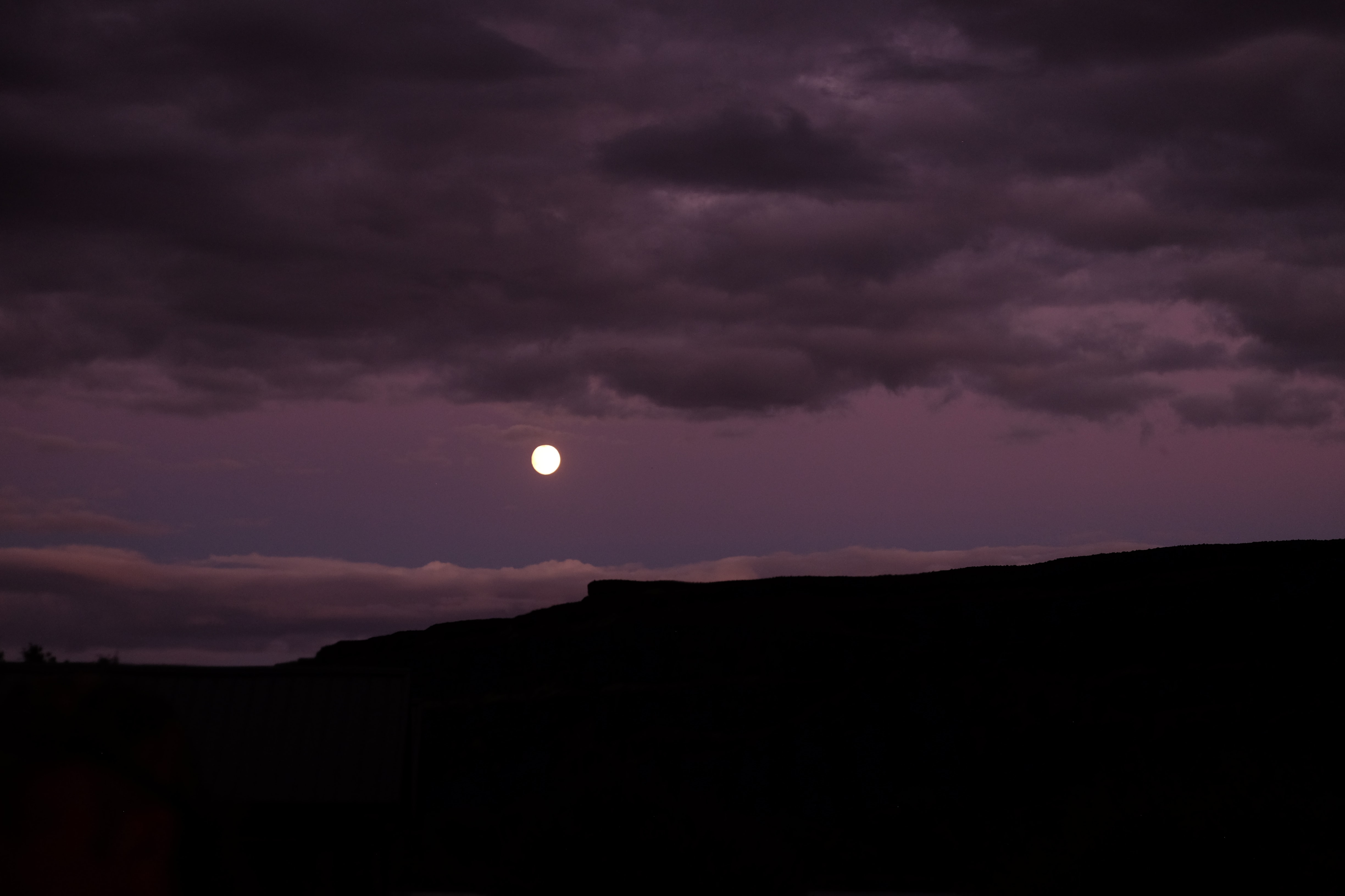 moon under clouds during night time