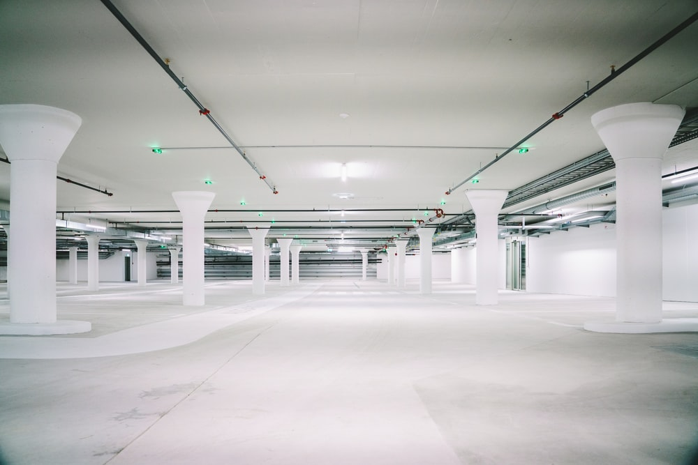 empty white concrete pillared parking lot