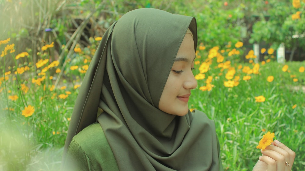 woman in gray hijab holding yellow flower