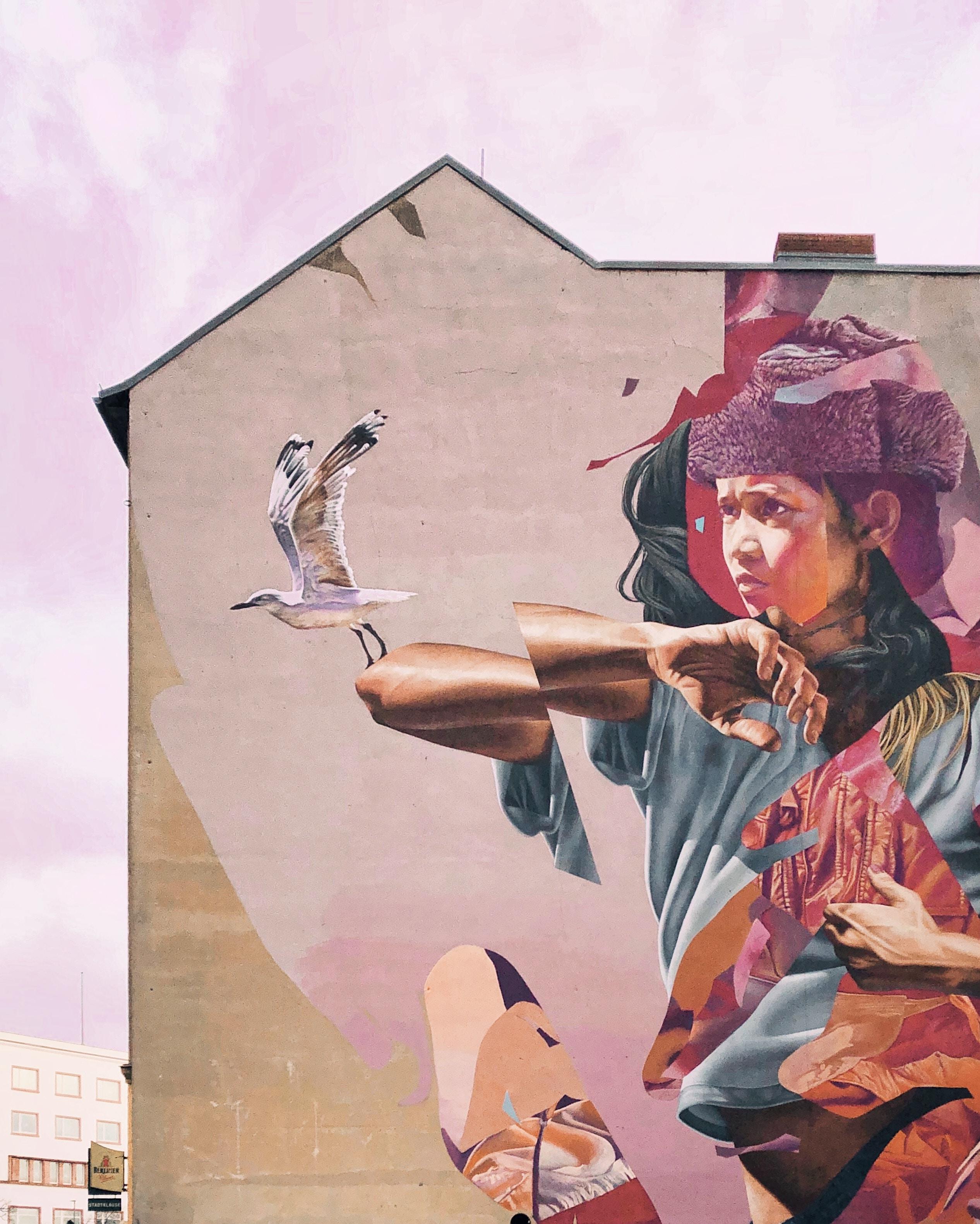 bird perch on boy's arm building graffiti
