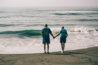 man and woman holding hands together while standing on seashore