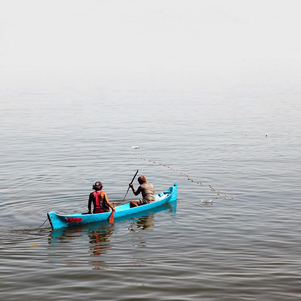 2 person in boat at body of water
