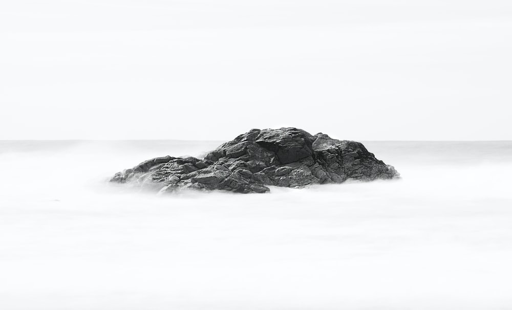 rock formation between body of water