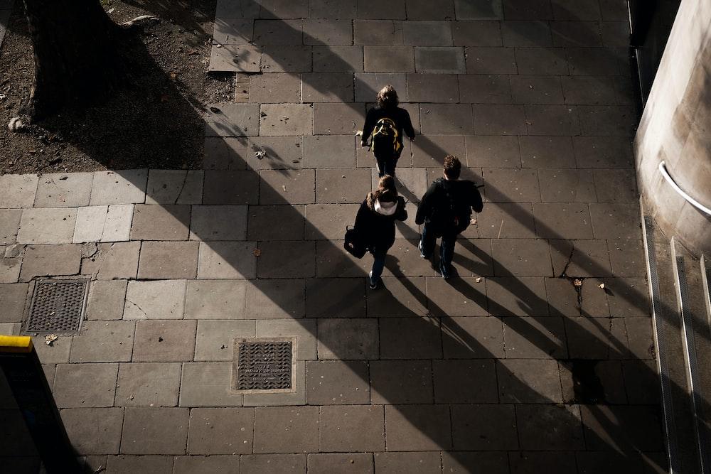 three people walking on concrete pavement
