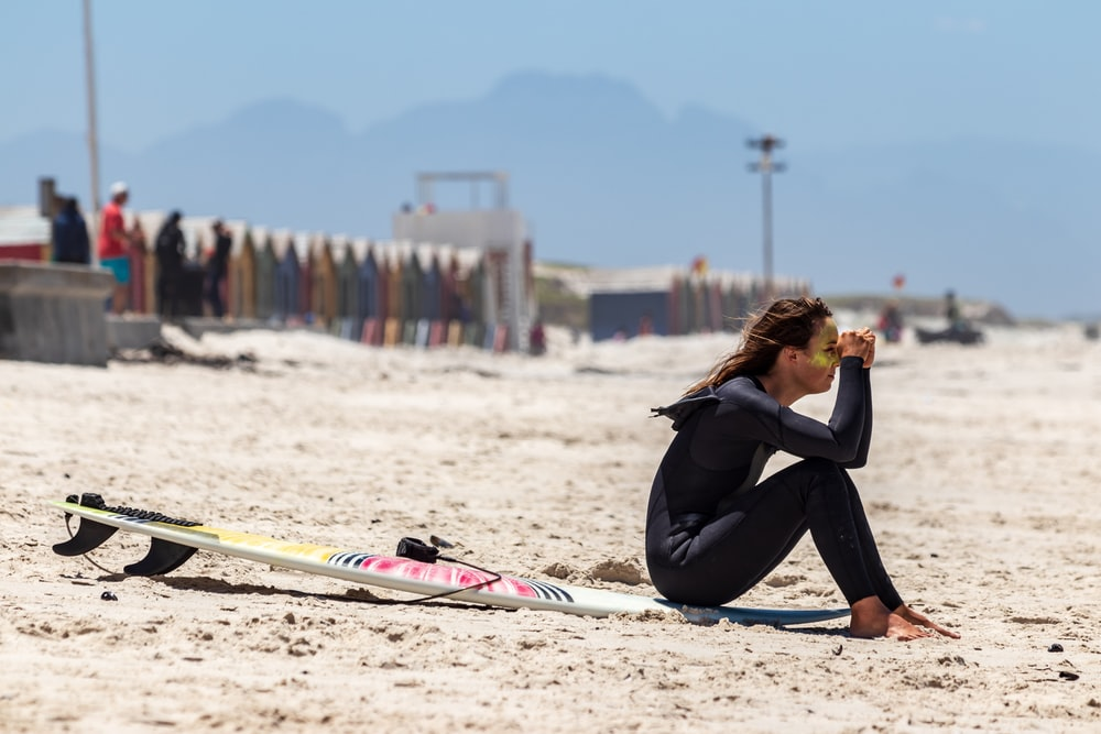 woman in wet suit sitting on surfing sofa