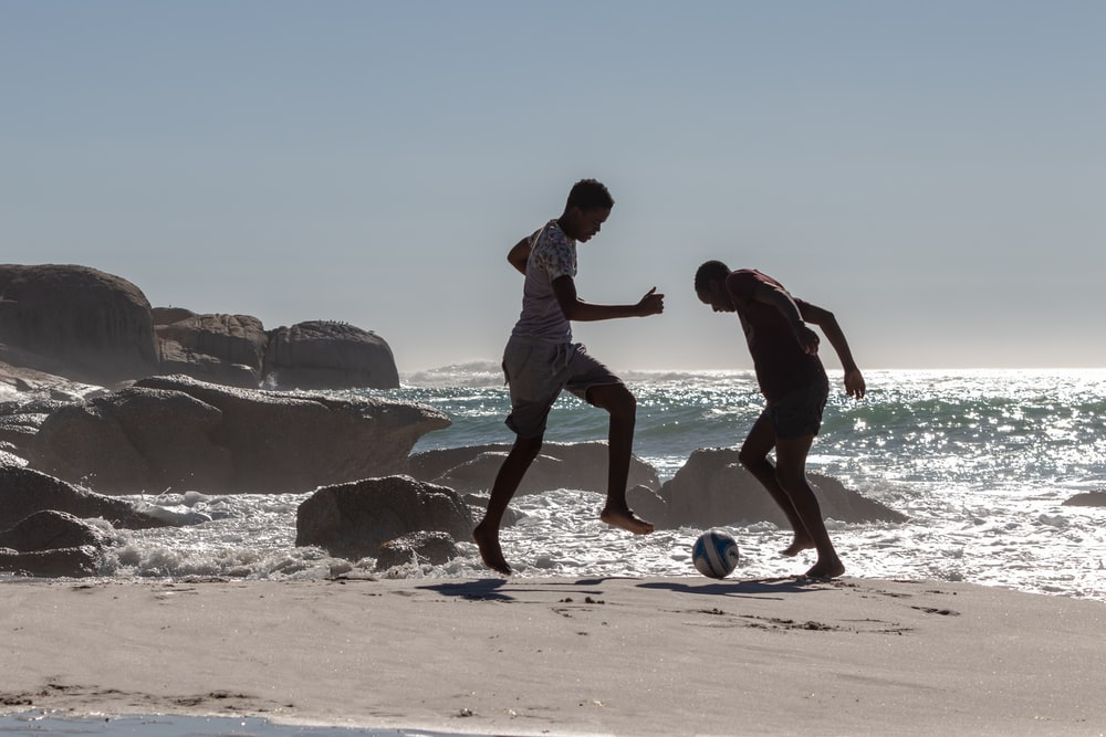 two men playing with soccer ball near seashore