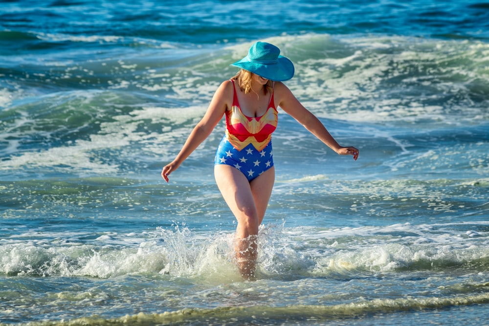 woman in wonder-woman bikini walks on sea waves
