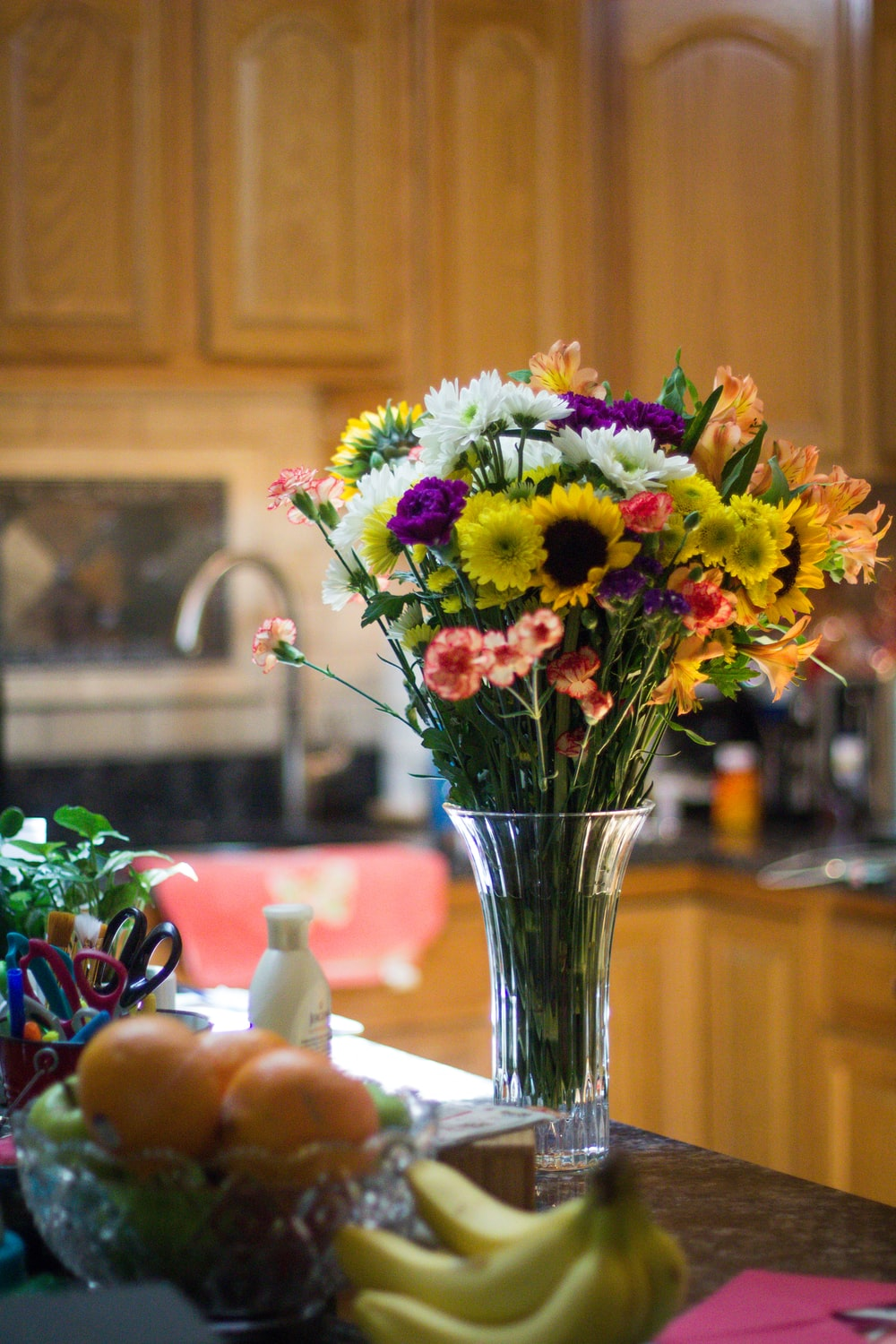 assorted-color petaled flowers on clear glass vase