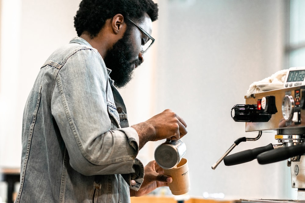 man pouring liquid on mug from can