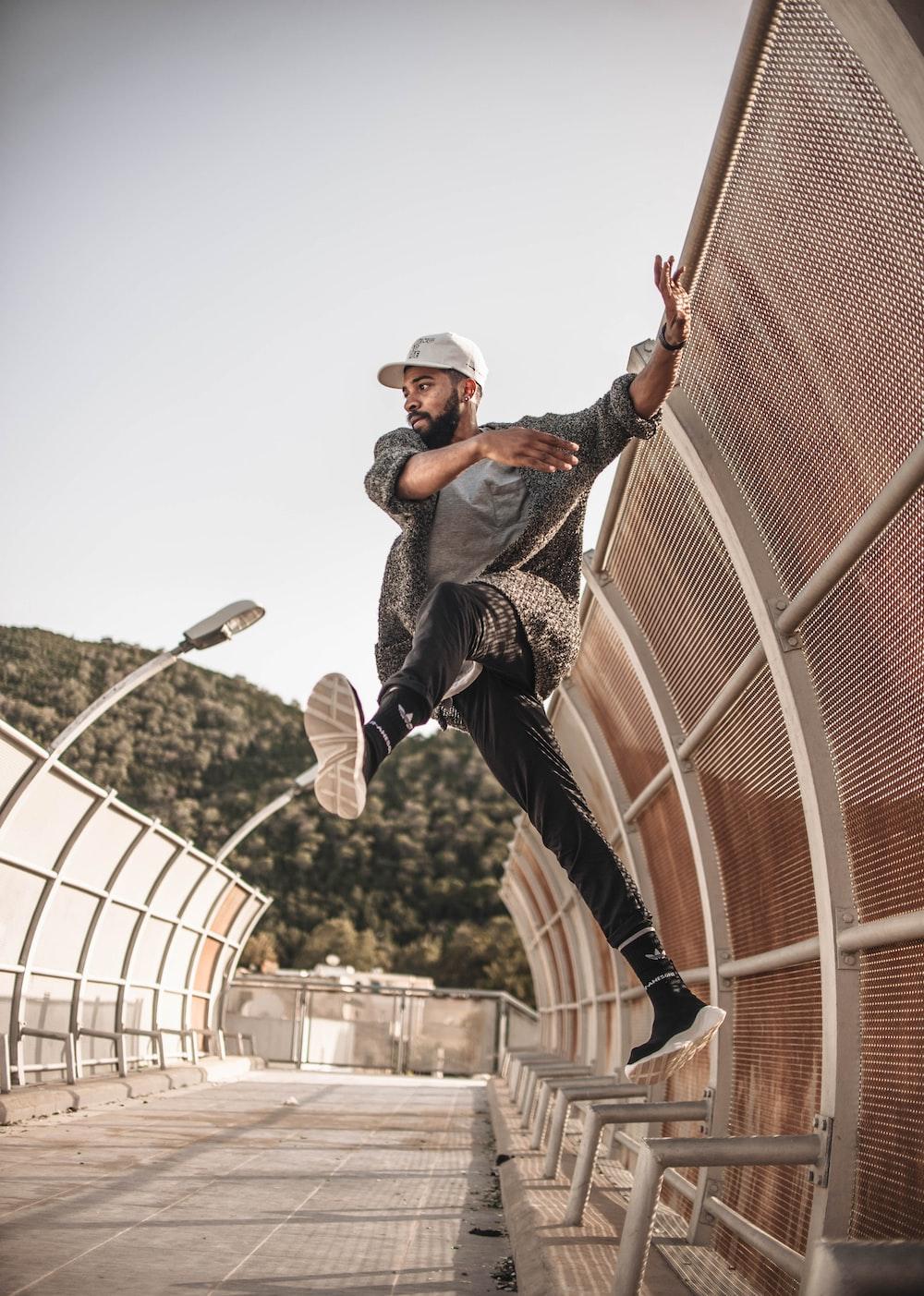 man jumping on gray metal railings
