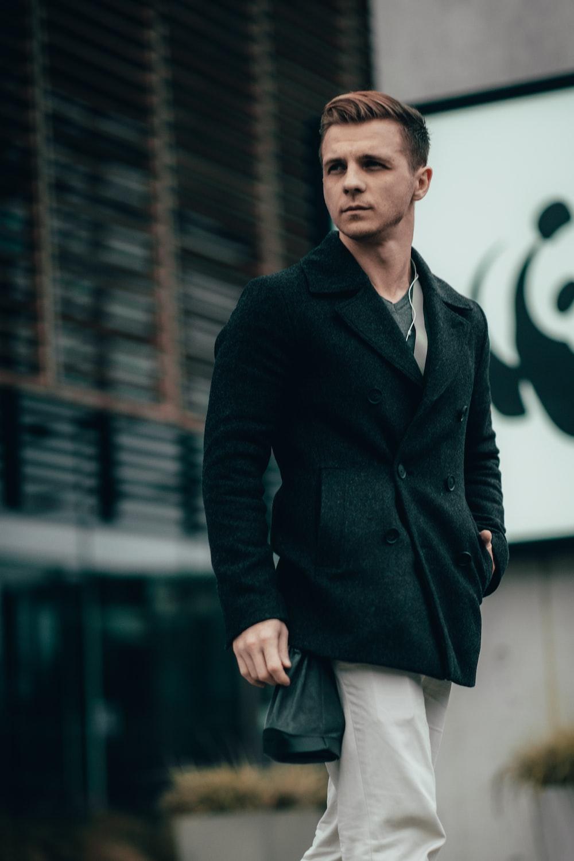 man in black coat walking on selective focus photograph