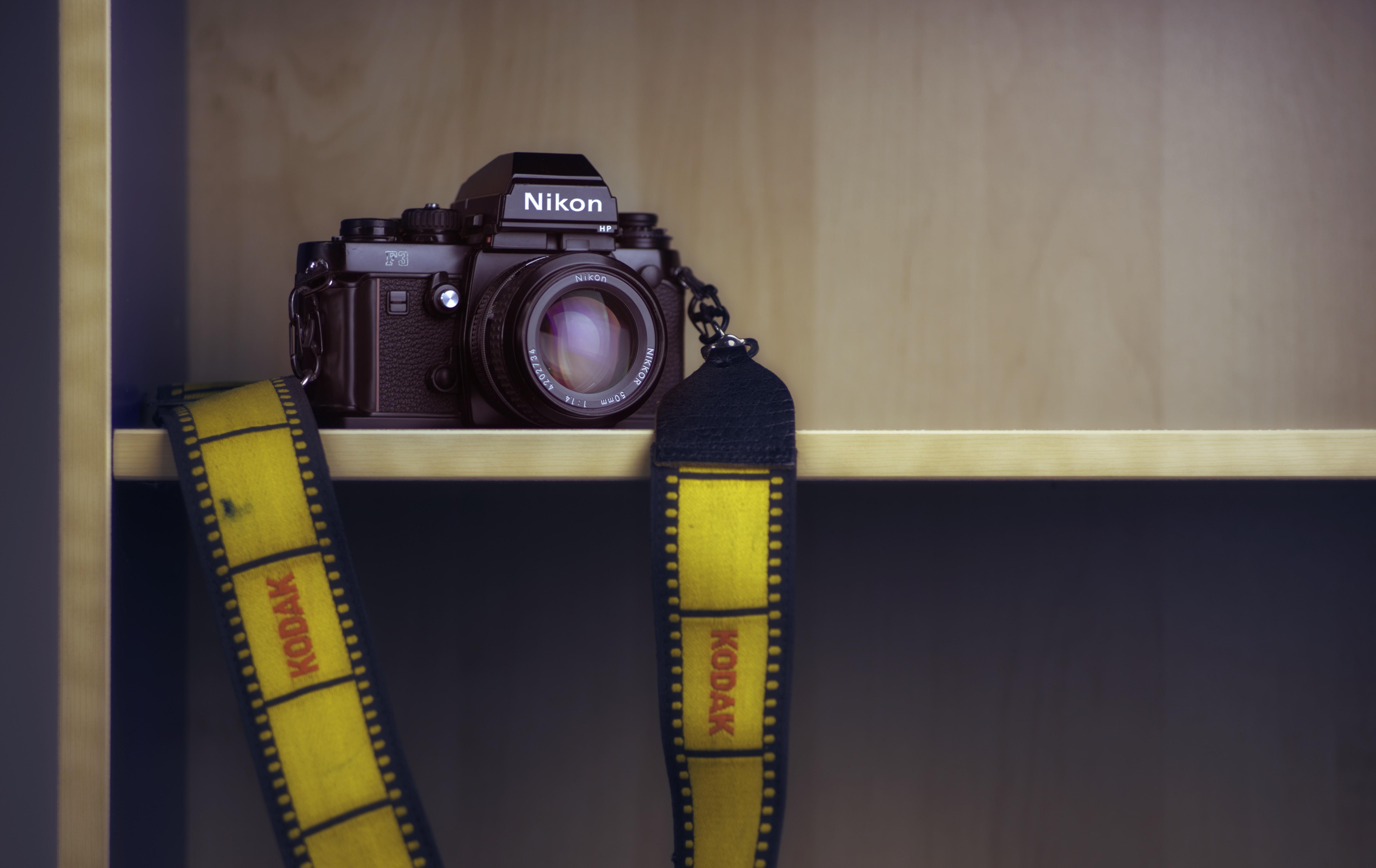black Nikon DSLR camera on brown wooden shelf