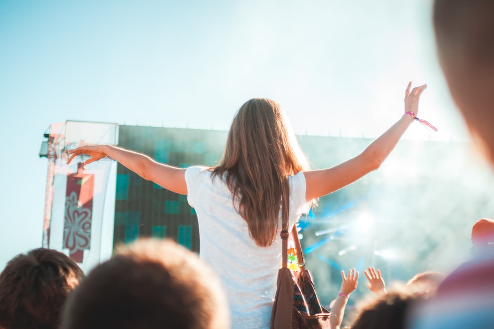 woman in white shirt with shoulder bag standing at the concert