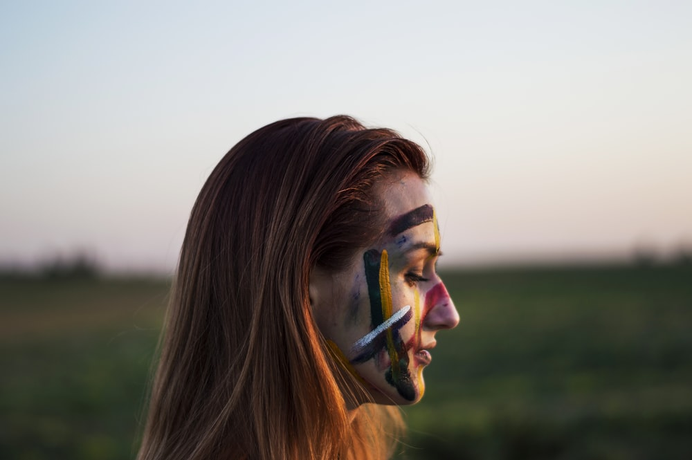 woman with face paint in selective focus photography