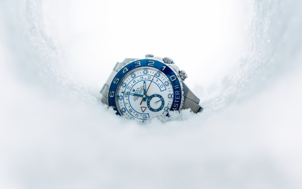 round silver-colored chronograph watch on snow