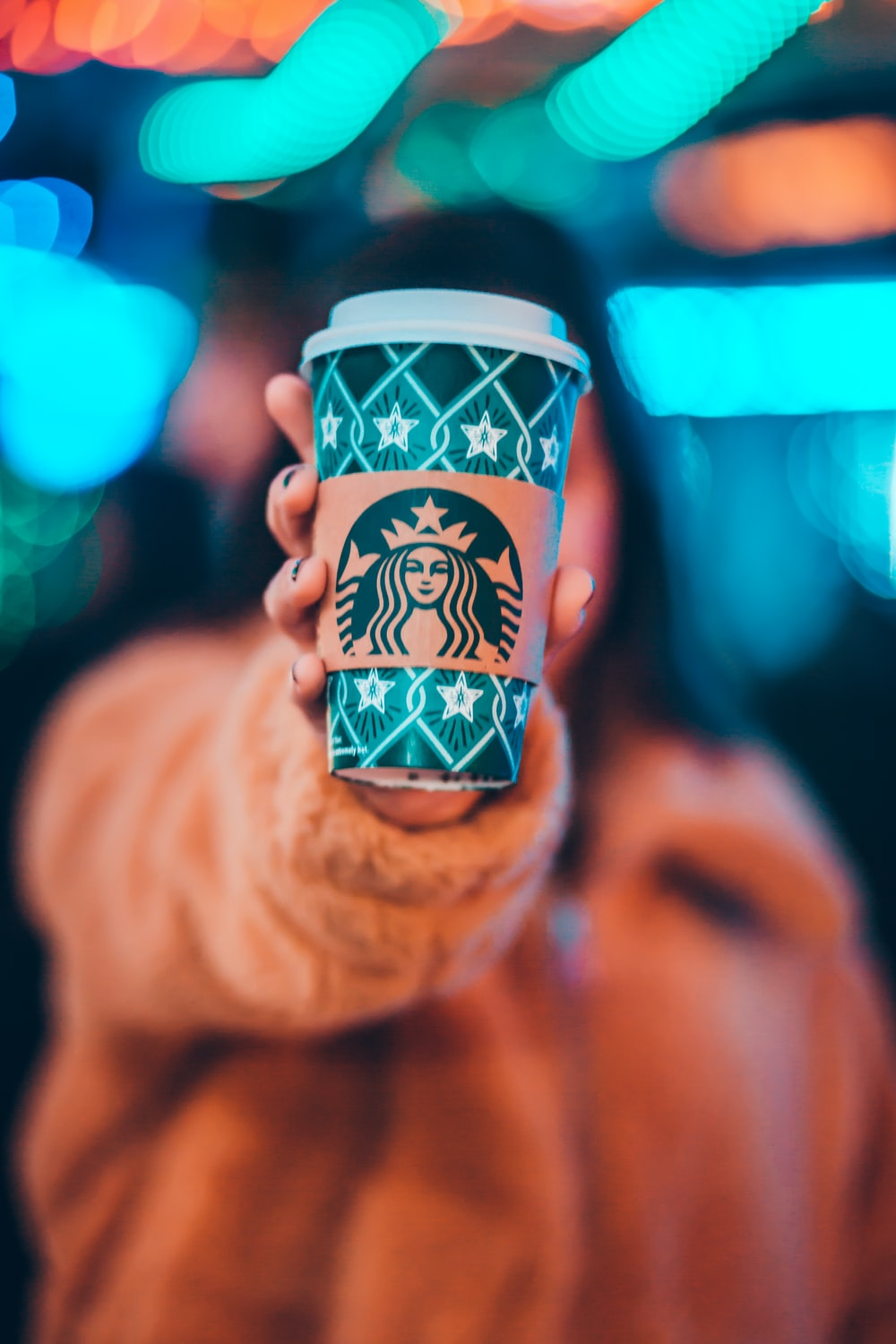 woman on brown jacket showing green and brown Starbucks coffee cup