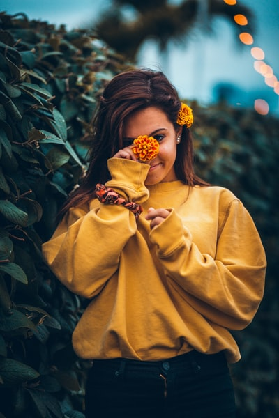 woman holding marigold flower by her face