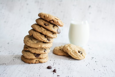 stack of cookies and glass of milk cookie teams background
