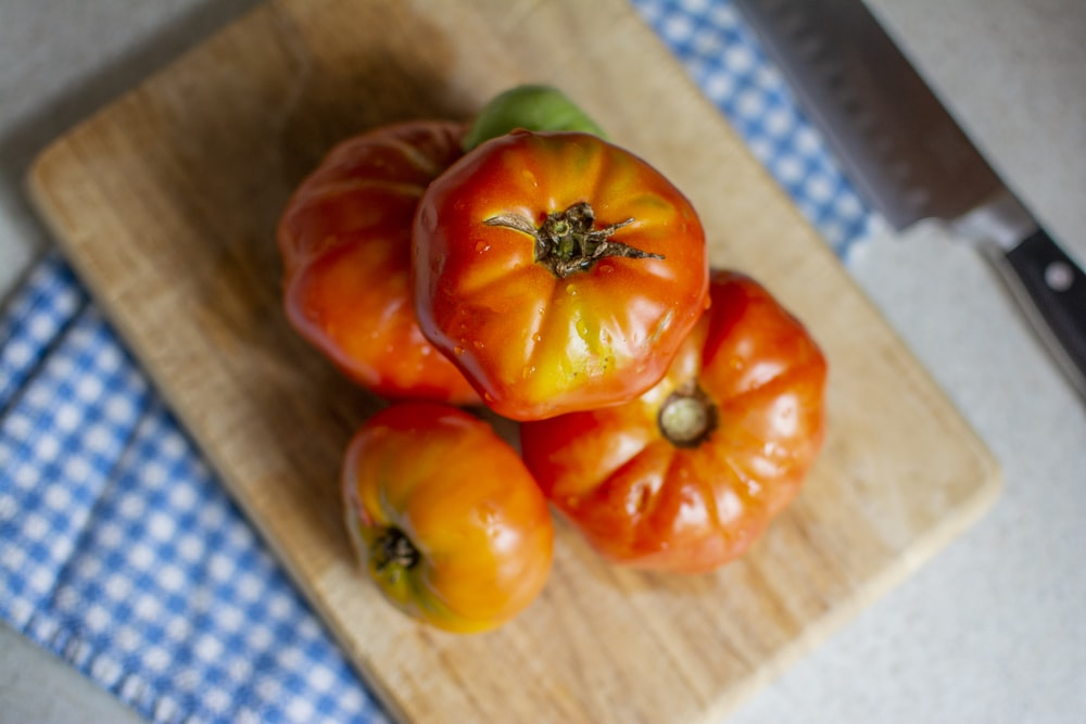 orange tomatoes on brown chopping board