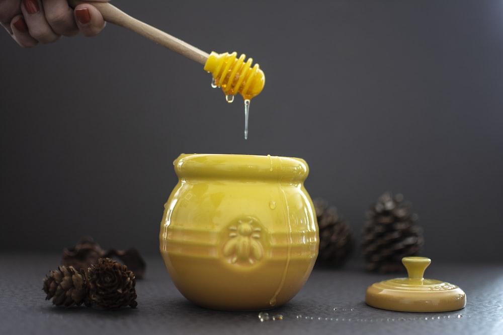 opened yellow ceramic jar beside pine cones