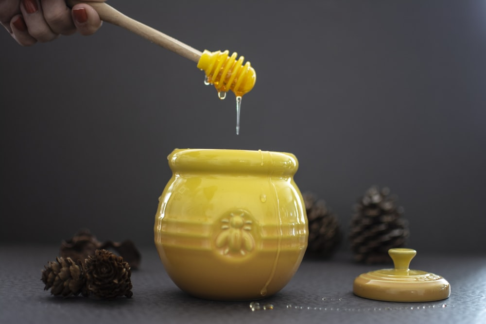 opened yellow ceramic jar beside pine cones