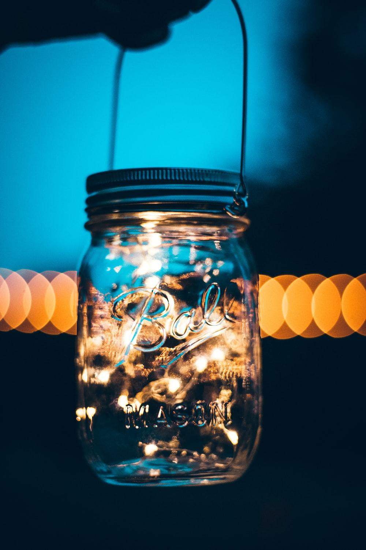 person holding glass mason jar