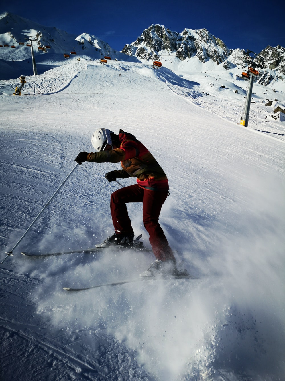 person in full suit with ski blades on snow covered field