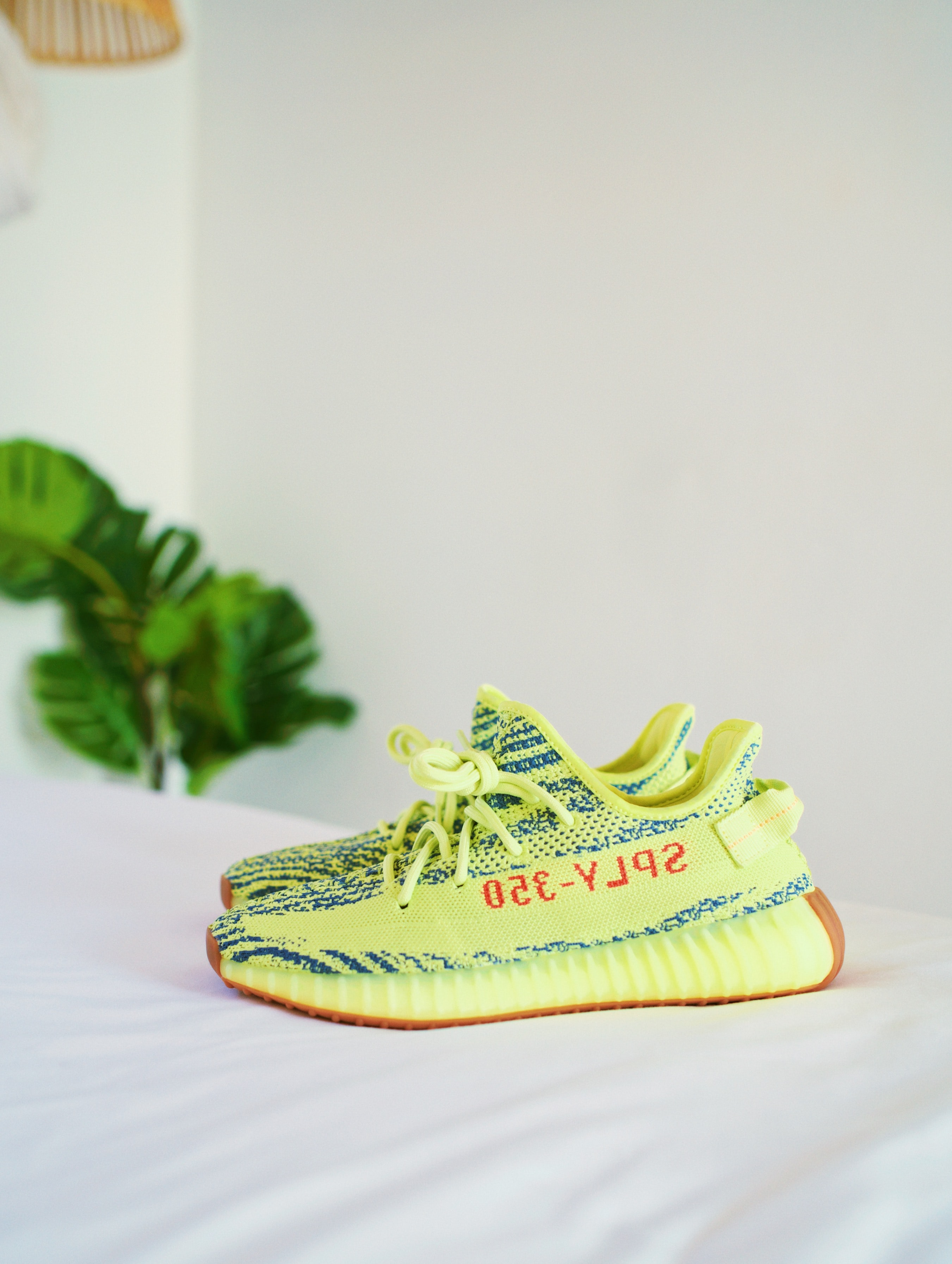 frozen yellow Adidas Yeezy Boost v2's on white bedspread
