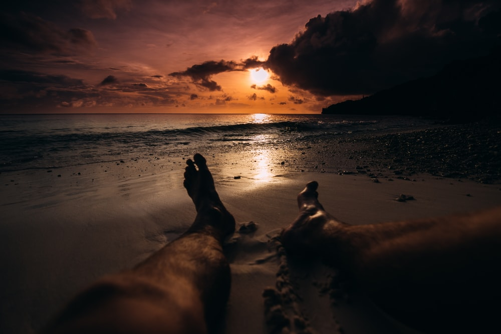 person lying on beach sand