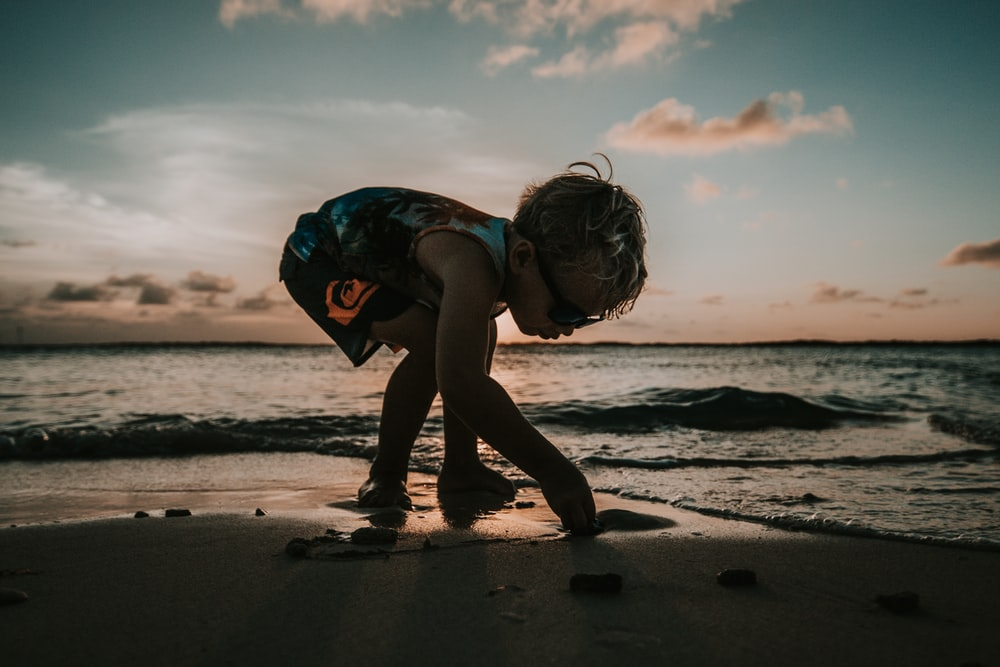 boy picking up sand