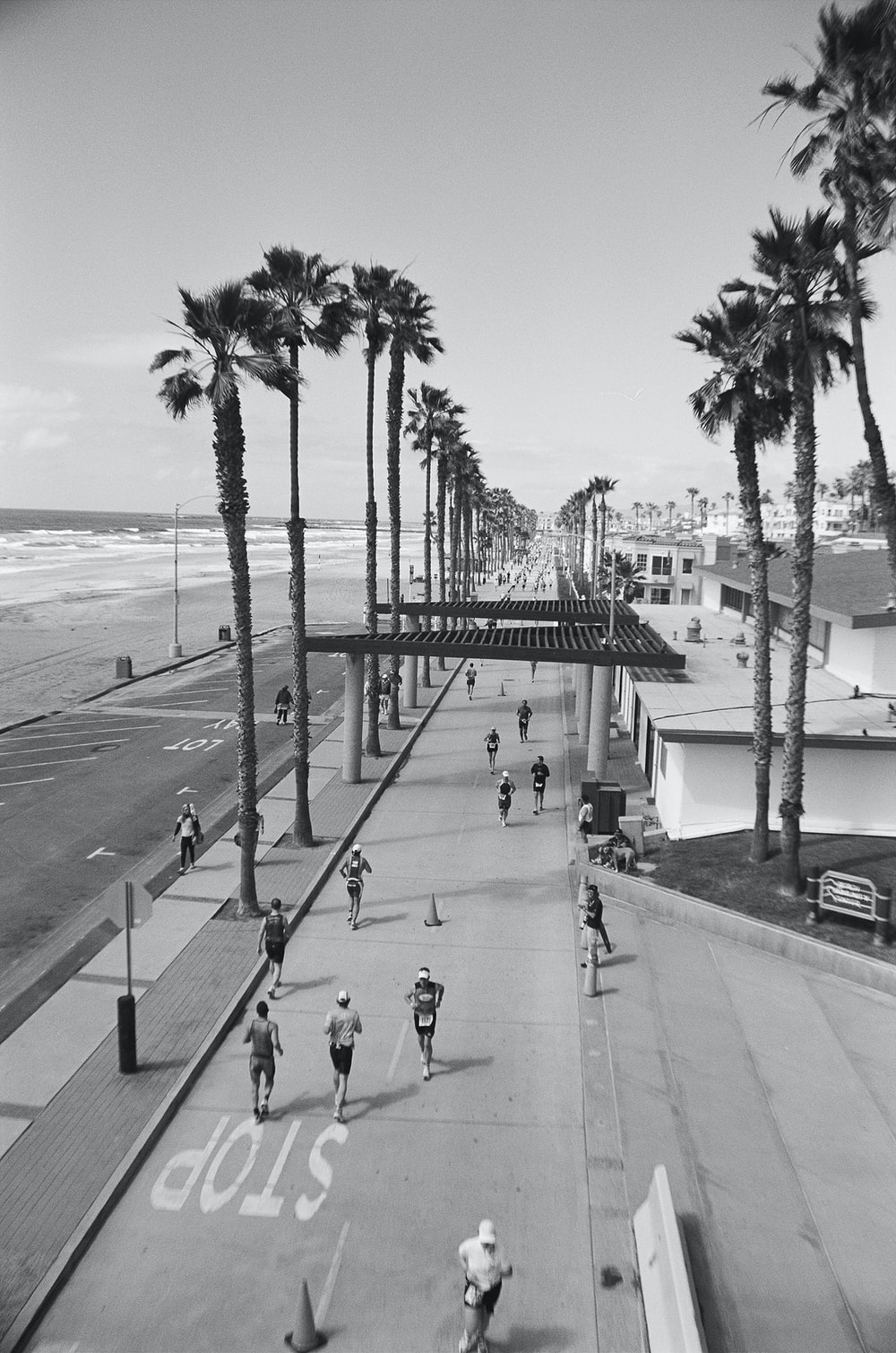 grayscale photo of people running near body of water