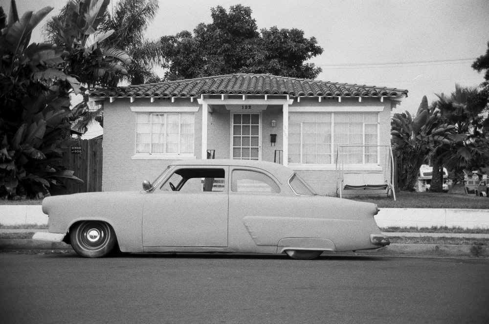 grayscale coupe parked on roadside