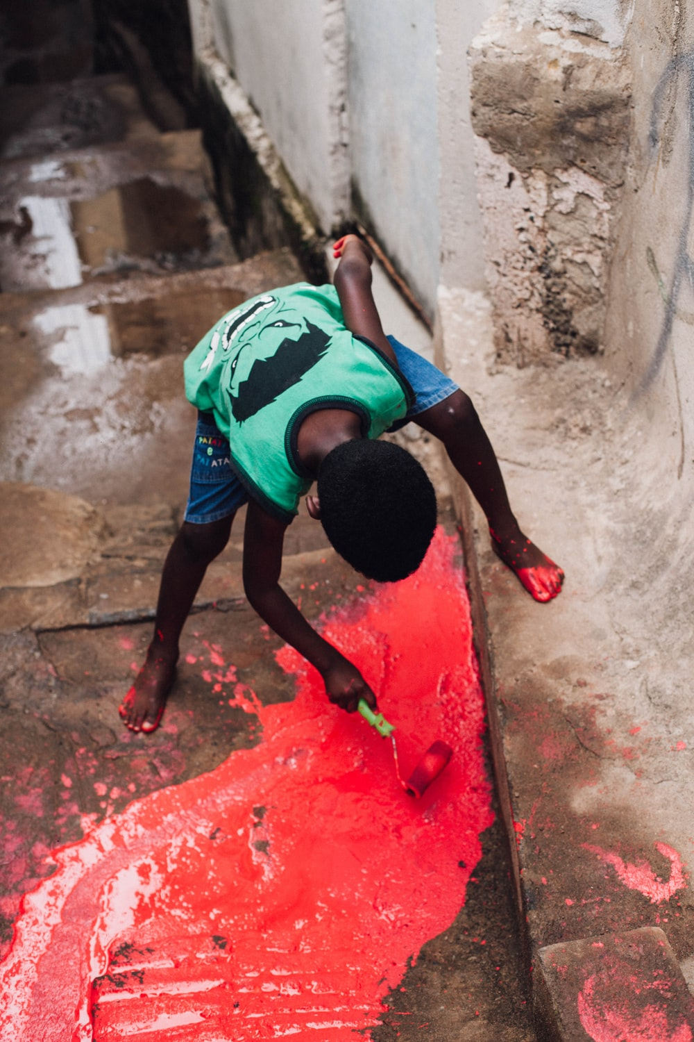 boy painting floor with red