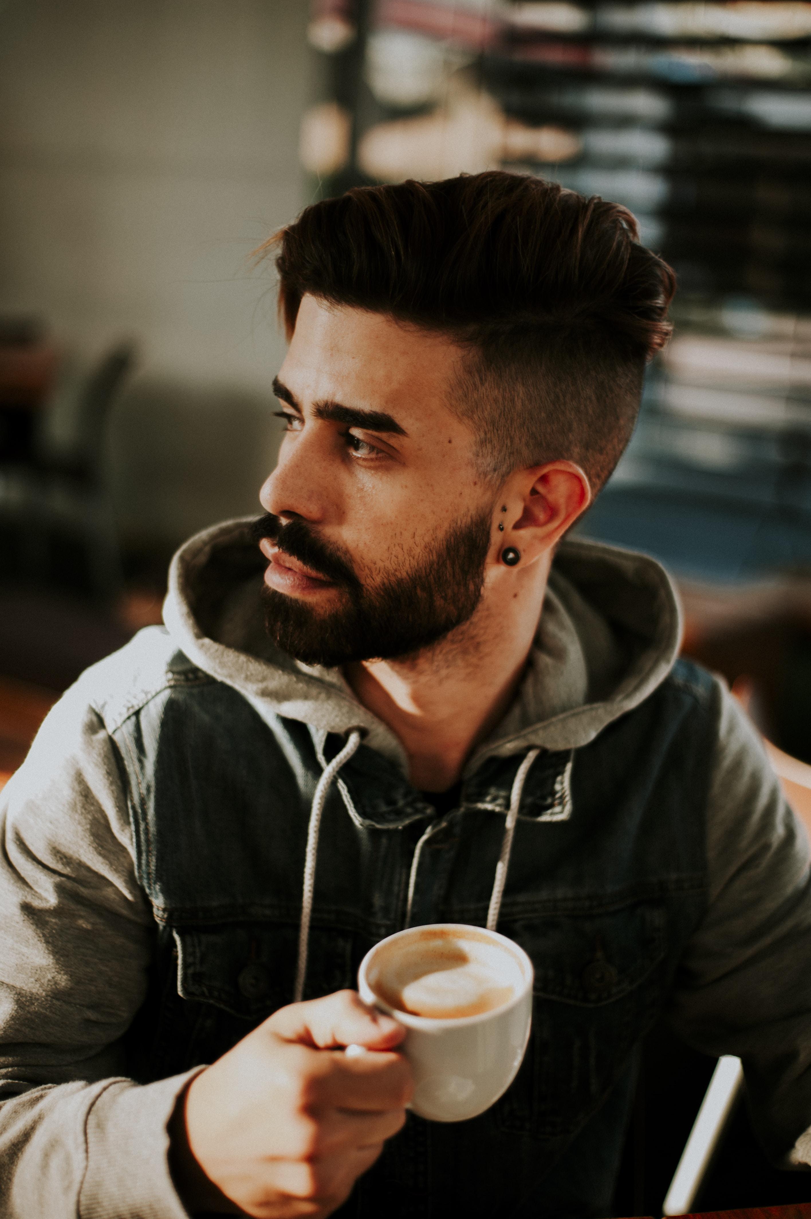 shallow focus photo of man in hoodie holding white ceramic mug