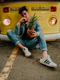 man holding pineapple while leaning on yellow van