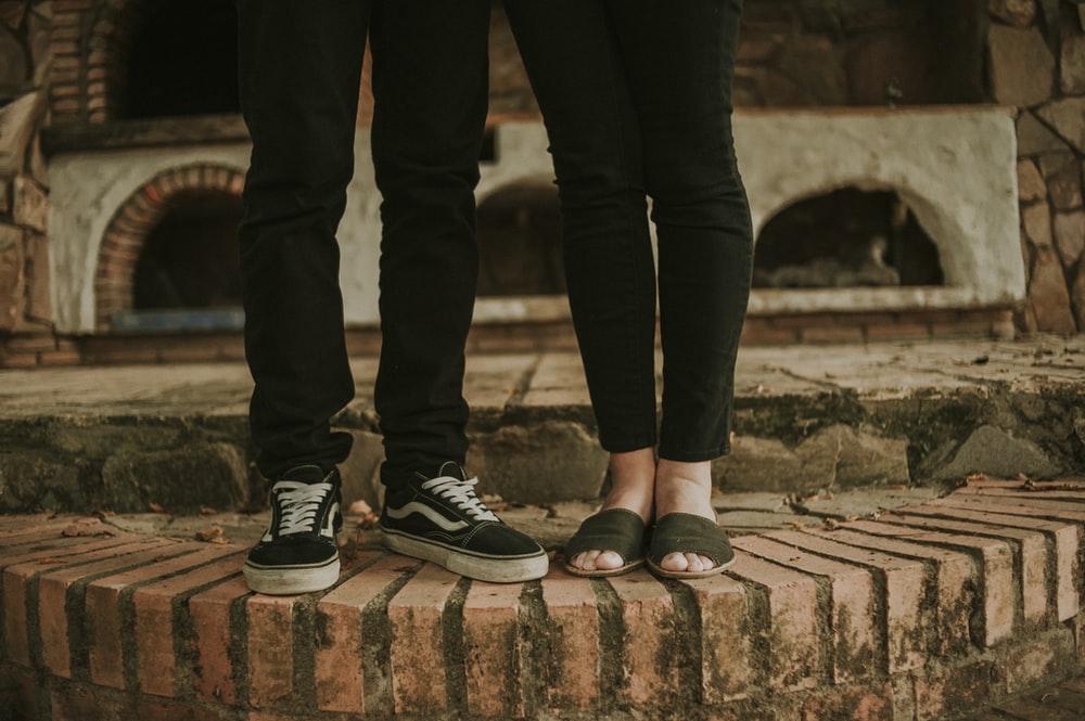 two persons standing on brown concrete floor