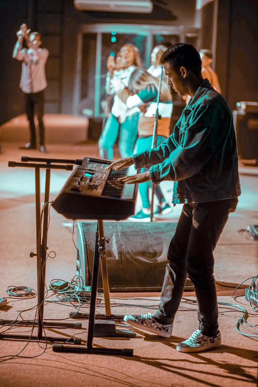 man in black jacket playing electric keyboard